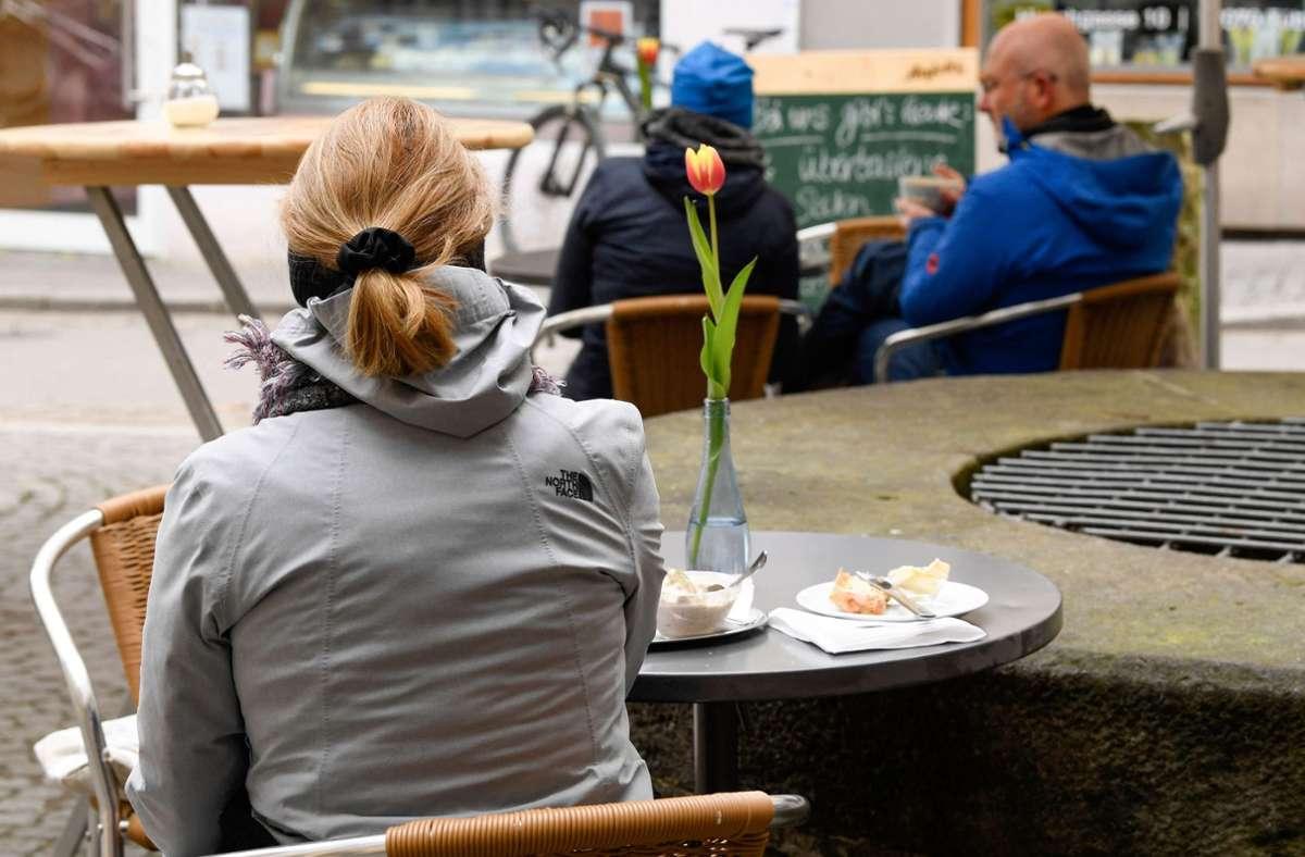 Eine Frau sitzt in Tübingen beim Kaffeetrinken. Foto: AFP/THOMAS KIENZLE