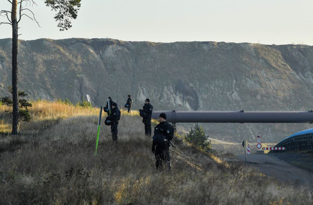 Polizeibeamte sichern ein Transportband für Braunkohle im Braunkohletagebau Jänschwalde in Brandenburg. Foto: dpa/Patrick Pleul