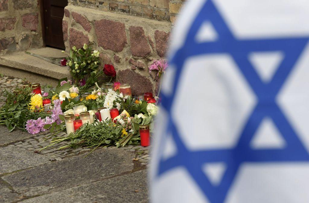Vor der Synagoge in Halle wurden Blumen und Trauerkerzen abgelegt. Foto: Jens Mayer/AP