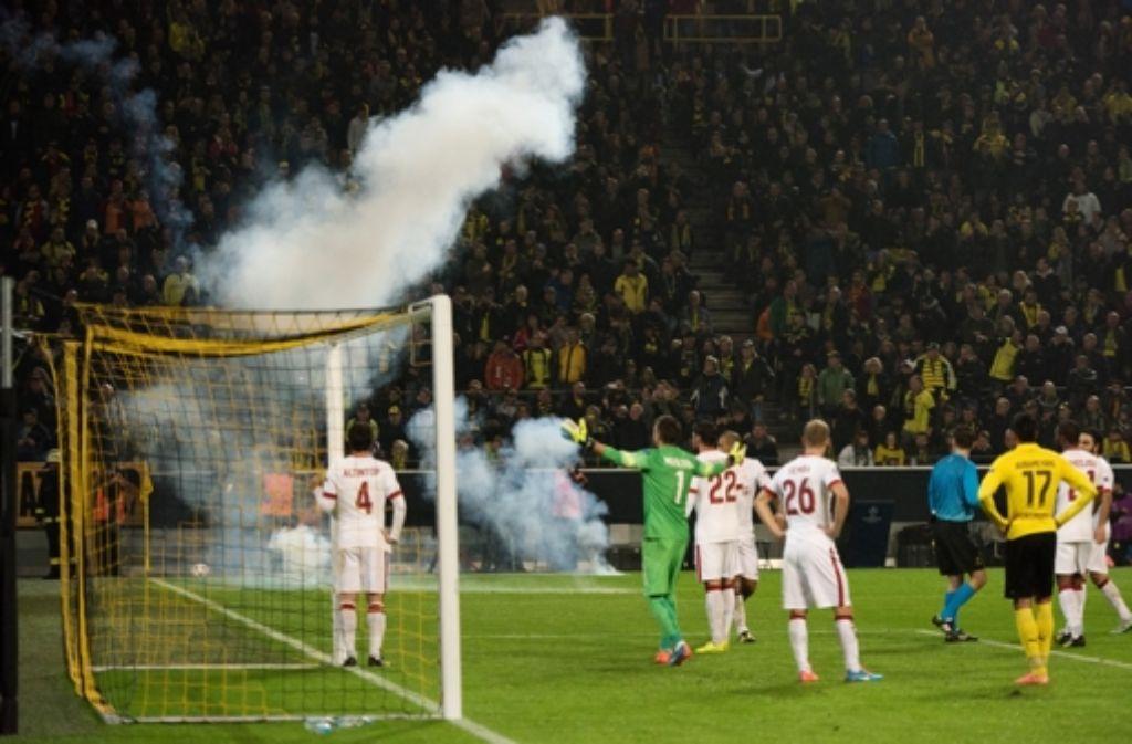 Feuerwekskörper und Rauchbomben fliegen in Dortmund aus dem Istanbuler Fanblock. Foto: dpa