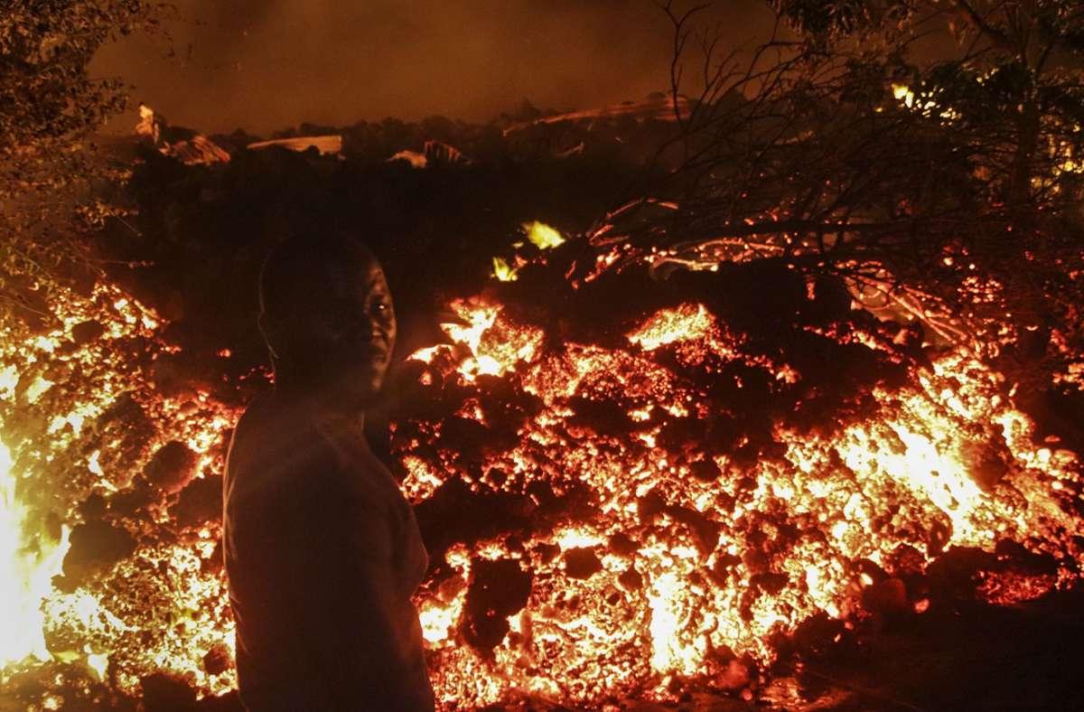 Eine Mann steht vor der Lava vom Ausbruch des Mount Nyiragongo in Buhene, am Stadtrand von Goma. Der kongolesische Berg Nyiragongo brach am 22. Mai  zum ersten Mal seit fast zwei Jahrzehnten aus. Foto: Justin Kabumba/AP/dpa