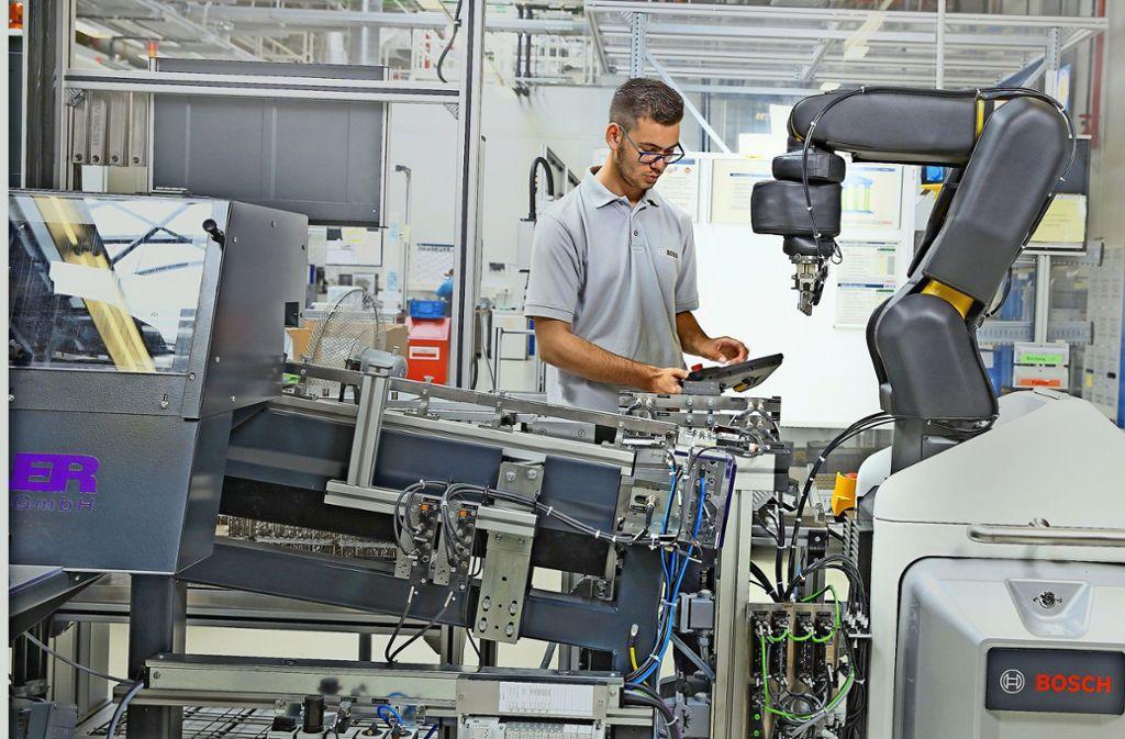 Mensch und Maschine arbeiten in der digitalen Fertigung Hand in Hand. Foto: Bosch