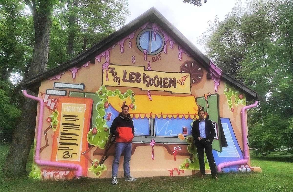 Lucas Wurmbach (links), einer der beiden Graffiti-Künstler, und Martin Binder, Leiter Netzentwicklung der Stuttgart Netze, stehen  vor dem neu gestalteten Umspannhäuschen an der Herrenberger Straße. Foto: Frank Wahlenmaier
