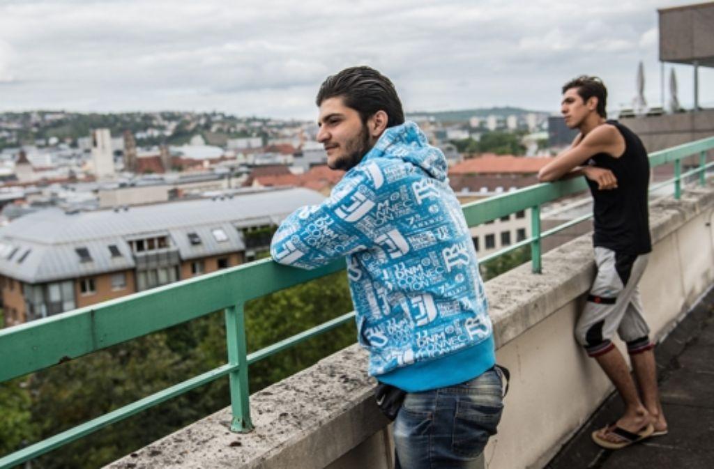 Zwei Männer stehen auf der Terrasse des Martinus-Hauses in Stuttgart. Das Gebäude dient seit dem Wochenende als Flüchtlingsunterkunft. Foto: dpa
