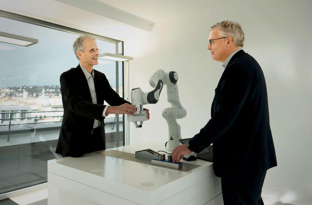 Der neue Voith-Chef Toralf Haag (rechts) und Roland Münch, der die Digitalsparte von Voith verantwortet, testen gemeinsam  den Leichtbauroboter Panda von Voith Robotics – ein Gemeinschaftsunternehmen mit dem Start-up Franka Emika. Foto: Voith