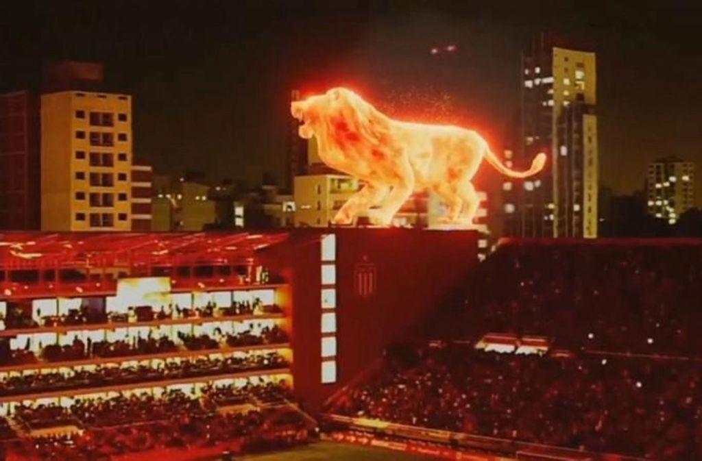 Der Feuerlöwe spaziert über das Tribünendach. Foto: Screenshot/Glomex