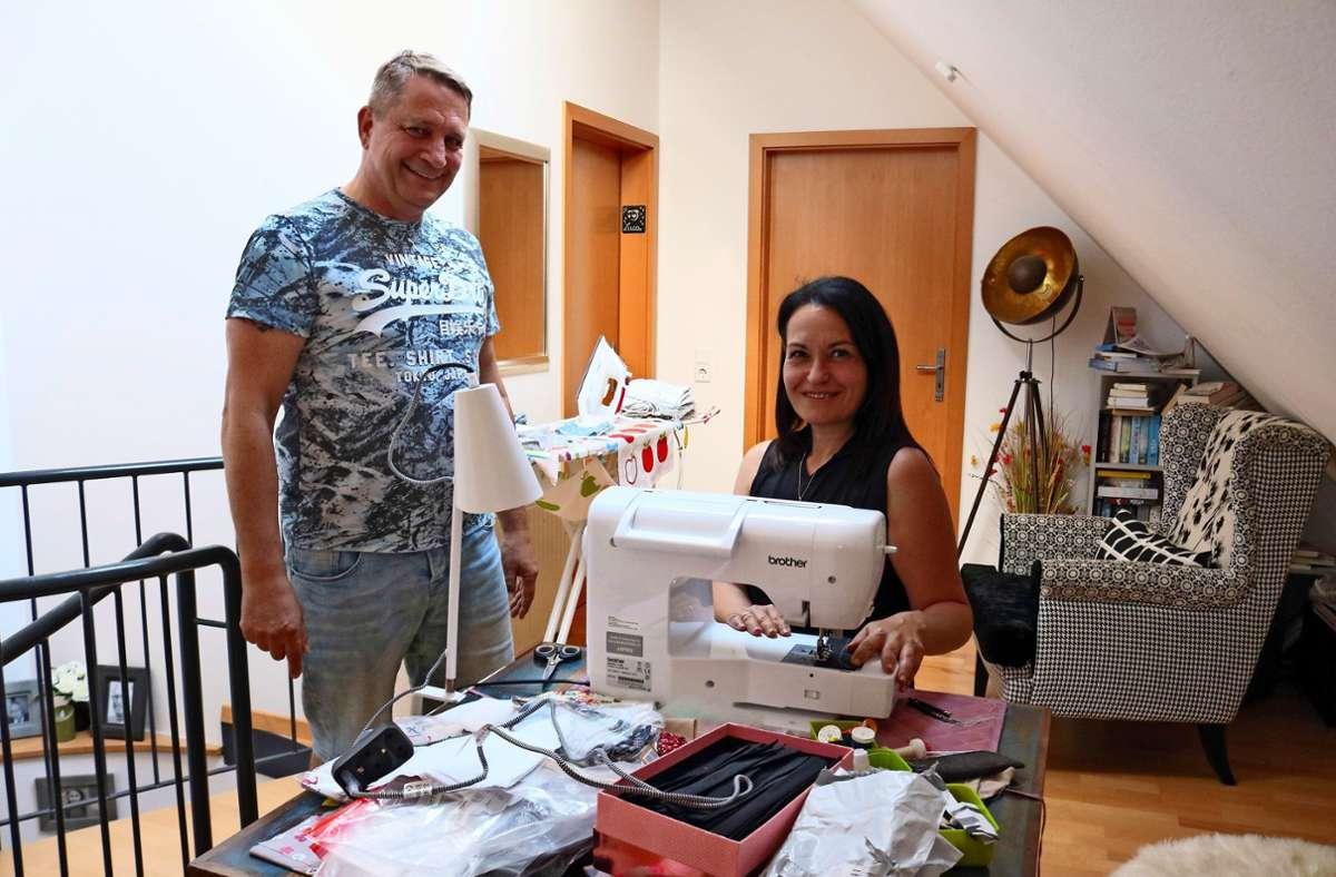Ein gewohntes Bild: Isabella Braun sitzt an der Nähmaschine, und  ihr Mann Stefan Büschel stärkt ihr den Rücken. Foto: Eva Herschmann