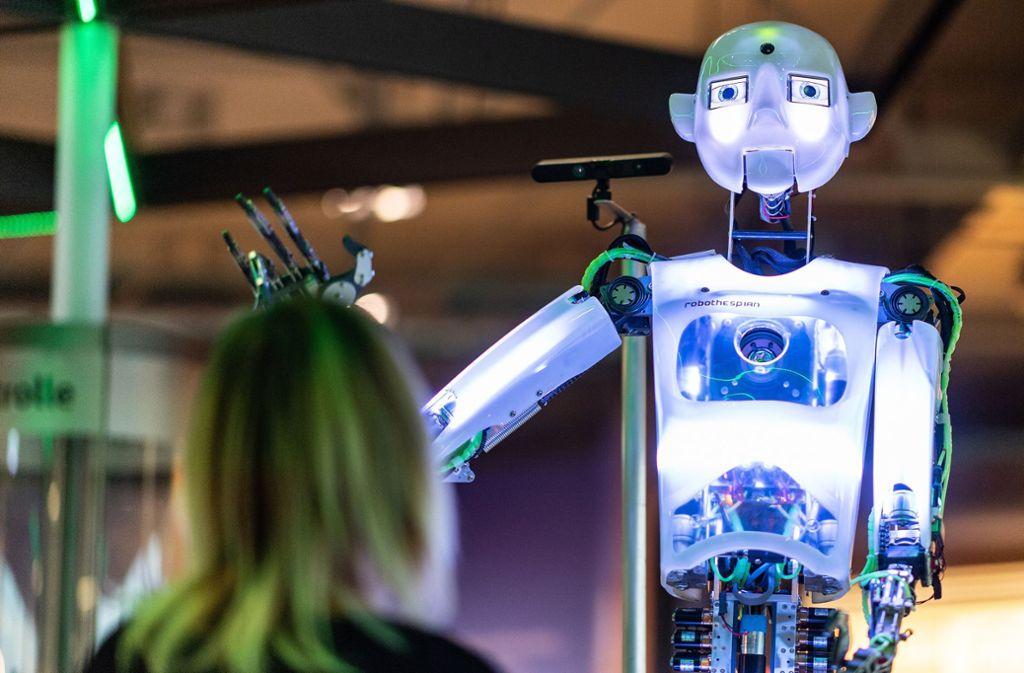 Eine Frau betrachtet einen Roboter im Heinz Nixdorf Museumsforum in Paderborn. Foto: dpa