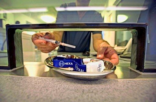 Aus dem Sicherheitsbereich wird dem Süchtigen die Heroinspritze gereicht, die er sich unter Aufsicht selbst setzt. Foto: Michael Steinert