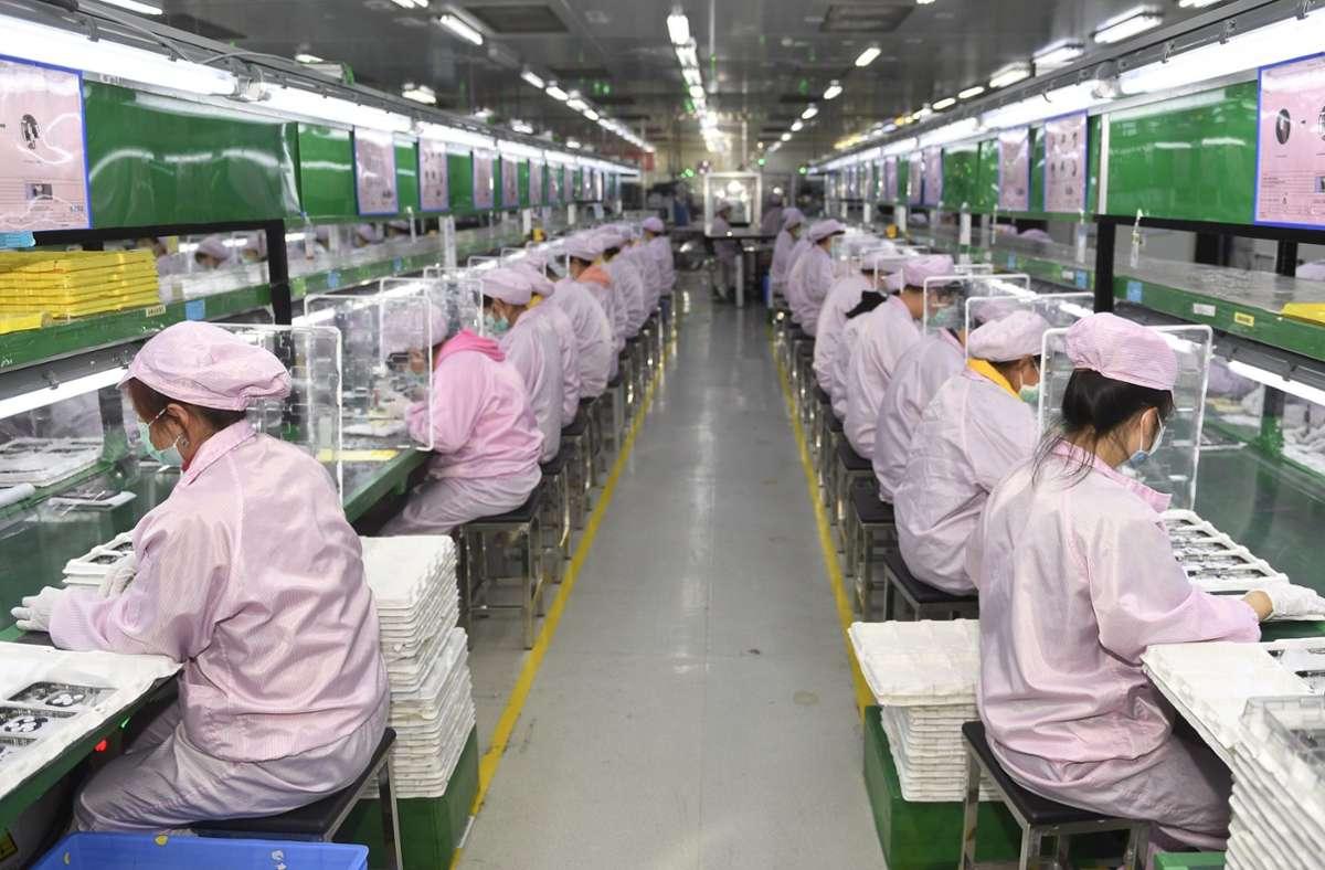 Arbeiter an den Produktionslinien in der Werkstatt der Jabil Technology (Chengdu) Co., Ltd. in Chengdu. Die Kommunistische Partei einwirft einen neuen  Fünf-Jahres-Plan, der China unabhängiger von der Welt machen soll. Foto: dpa/Liu Kun