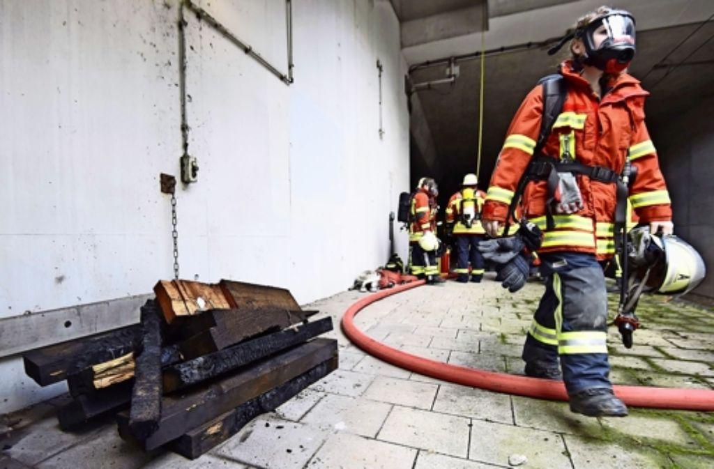 Feuerwehrleute mussten unter schwerem Atemschutz einen Brand im Echterdinger S-Bahn-Tunnel löschen. Feuer gefangen hatten Holzbohlen (links), die zur Sicherheitsausstattung des Tunnels gehören. Foto: 7aktuell.de/Eyb