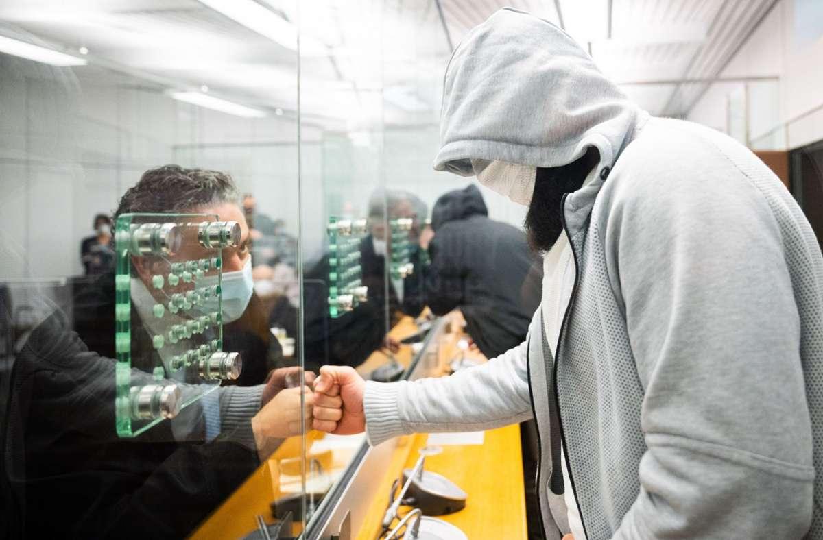 Abu Walaa (rechts), mutmaßlicher Anführer der Terrormiliz Islamischer Staat (IS) in Deutschland, begrüßt im Oberlandesgericht in Celle durch eine Glasscheibe seinen Anwalt Thomas Koll. Foto: dpa Pool/Julian Stratenschulte