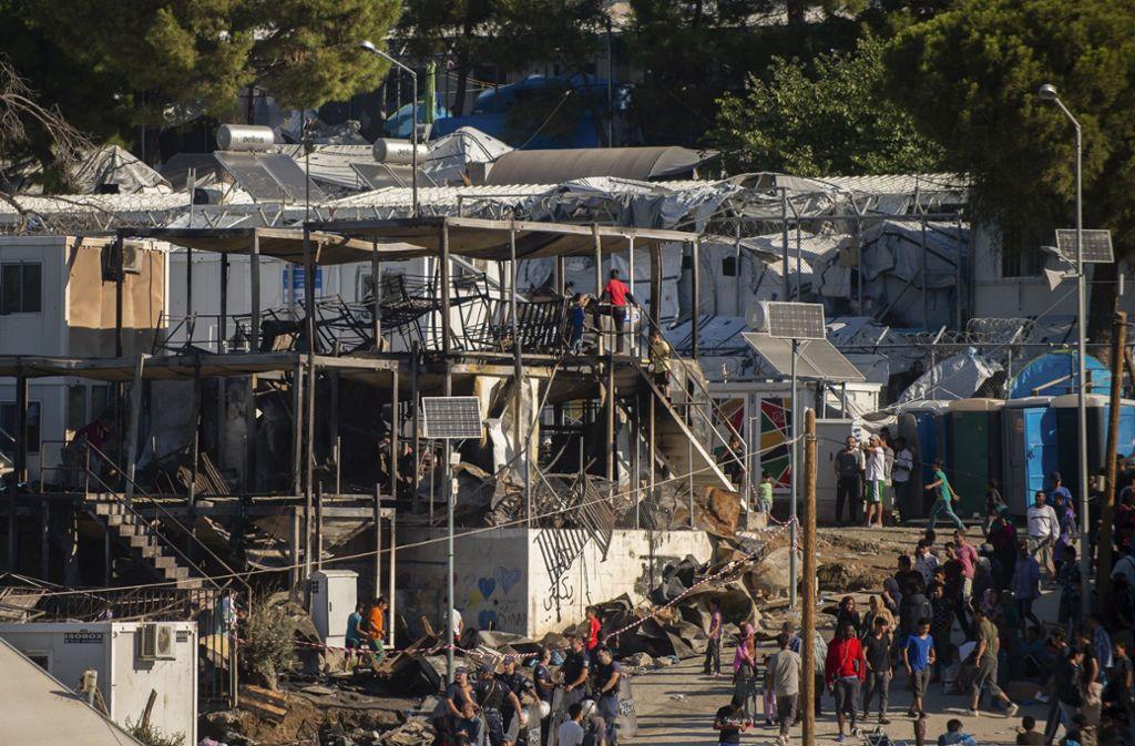 Migranten und Flüchtlinge stehen neben ausgebrannten Hauscontainern im Flüchtlingslager Moria. Foto: dpa/Angelos Tzortzinis
