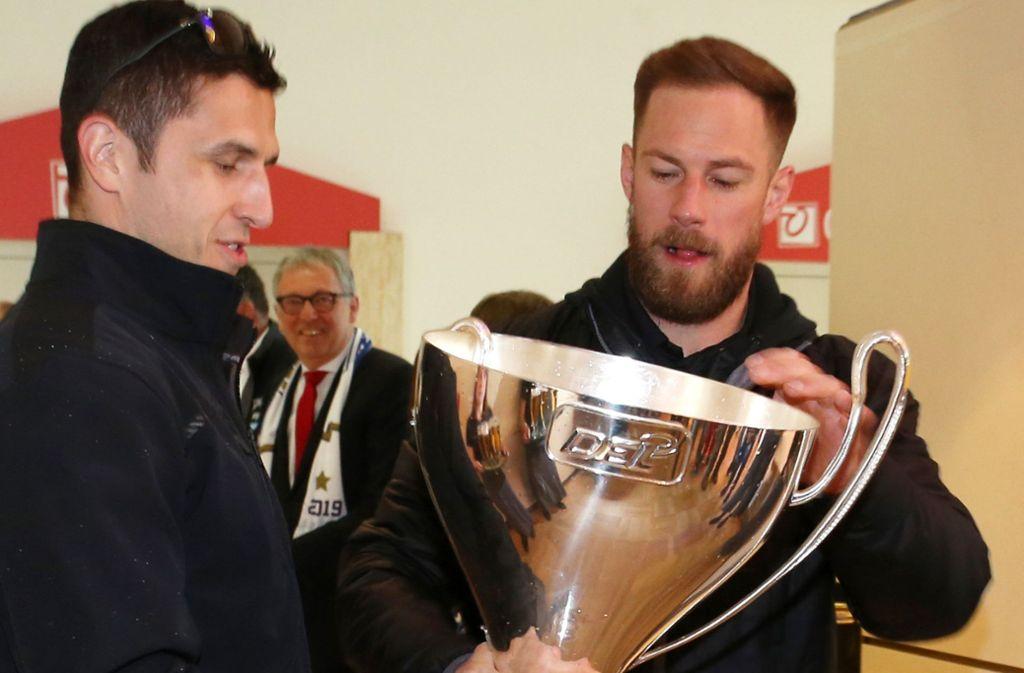 Marcel Goc (links) trägt den Pokal und Markus Kink hängt den abgebrochenen Henkel in den Pokal. Foto: dpa