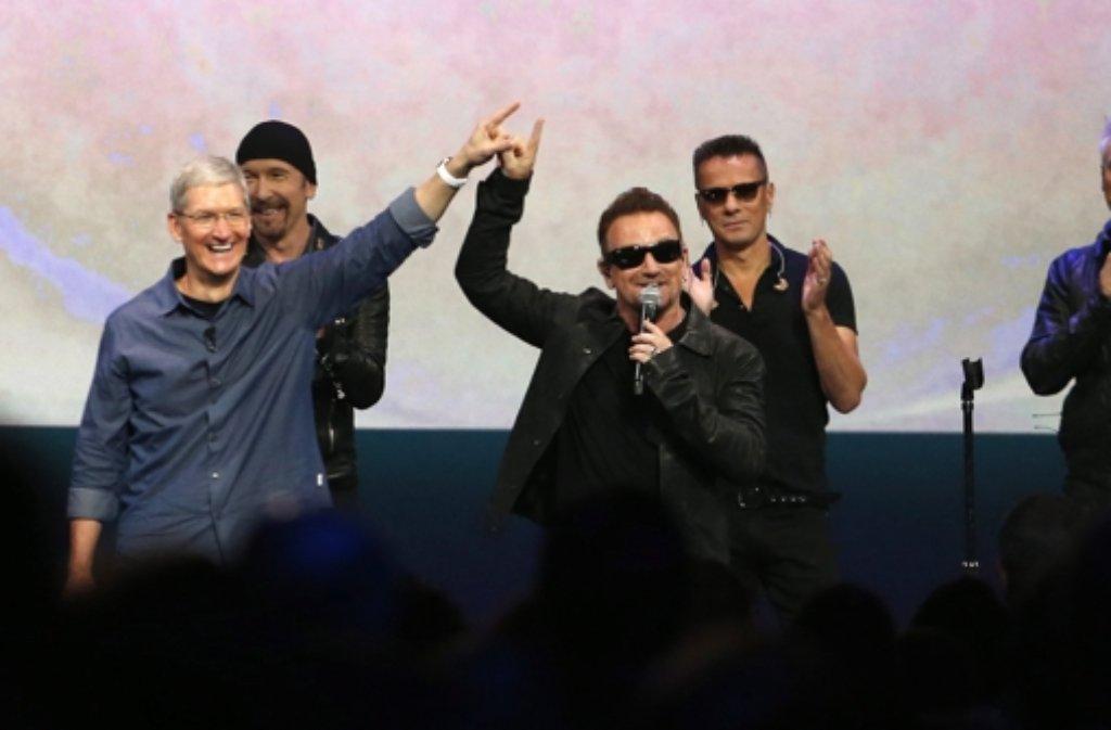Apple-Chef Tim Cook (links) mit dem Sänger der irischen Rockband Bono (dritter von rechts) bei der Keynote in Cupertino. Foto: dpa