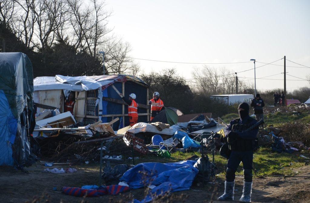 """Unter Polizeischutz reißen Arbeiter Anfang März im Flüchtlingslager von Calais, dem """"Dschungel von Calais"""", Hütten ab. Foto: dpa"""