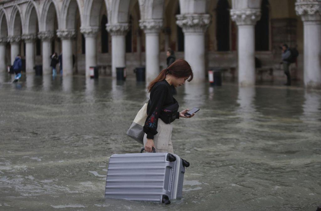 Überschwemmungen in Venedig. Eine Frau wartet mit ihrem Koffer durch das Wasser auf dem Markusplatz. Foto: dpa/Luca Bruno