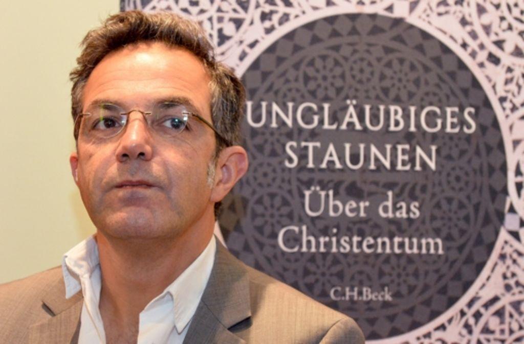 """Der deutsch-iranische Schriftsteller und Publizist Navid Kermani posiert während einer Signierstunde auf der Buchmesse in Frankfurt  vor einem Plakat, das sein Buch """"Ungläubiges Staunen - Über das Christentum"""" präsentiert. Foto: dpa"""
