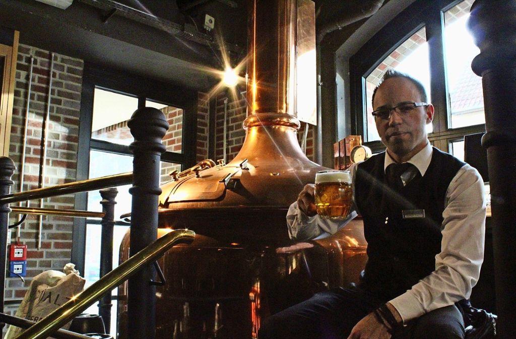 Christian Wassmer reicht ein selbst gebrautes Bier. Foto: Denise Kupka