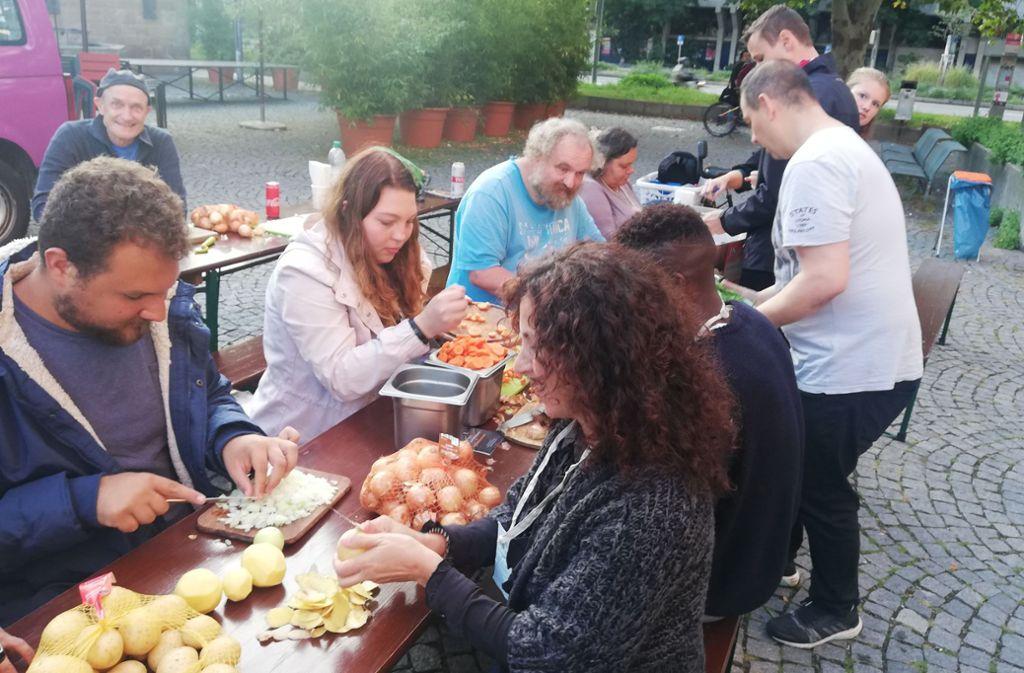 Anwohner schneiden Gemüse, um  mit dem Foodsharing-Projekt Common Kitchens einen Eintopf zu kochen. Die Lebensmittel wären sonst entsorgt worden. Foto: /Cedric Rehman