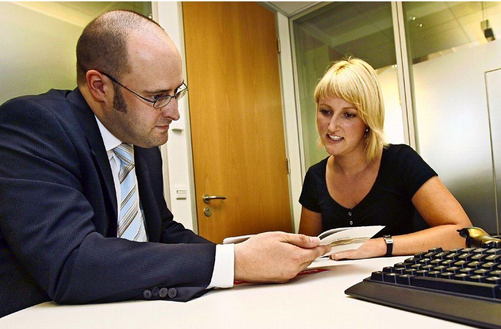 Ein Berater erklärt etwas über Wertpapiere: Die BW-Bank setzt nun wieder auf den persönlichen Austausch. Foto: dpa//Rolf Haid