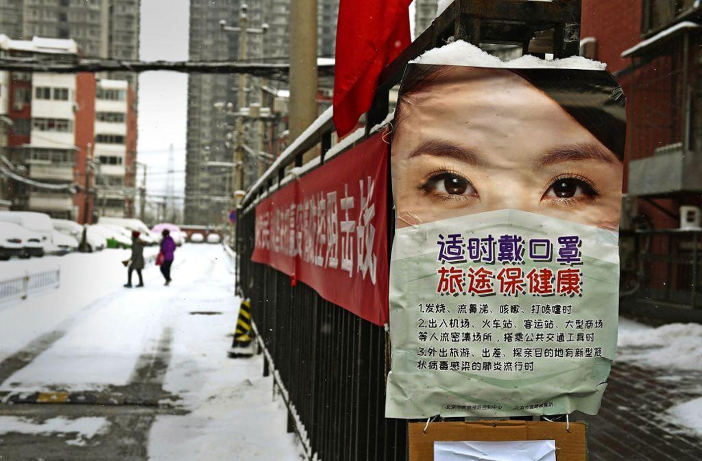 Ein Plakat vor einer Wohnanlage in Peking warnt vor Ansteckung mit dem Coronavirus. Foto: AFP/Greg Baker
