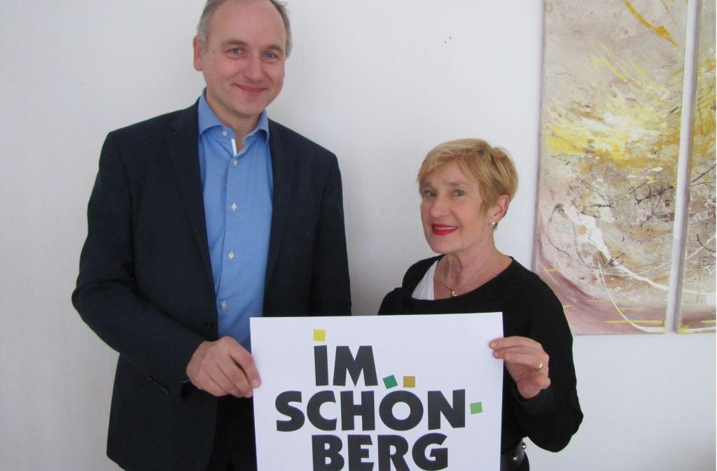 Veit Mathauer und Beate Mierendorf halten das neue Logo des Bürgervereins in die Kamera.   Der Schriftzug bildet die Umrisse des Stadtteils ab. Foto: Rehman
