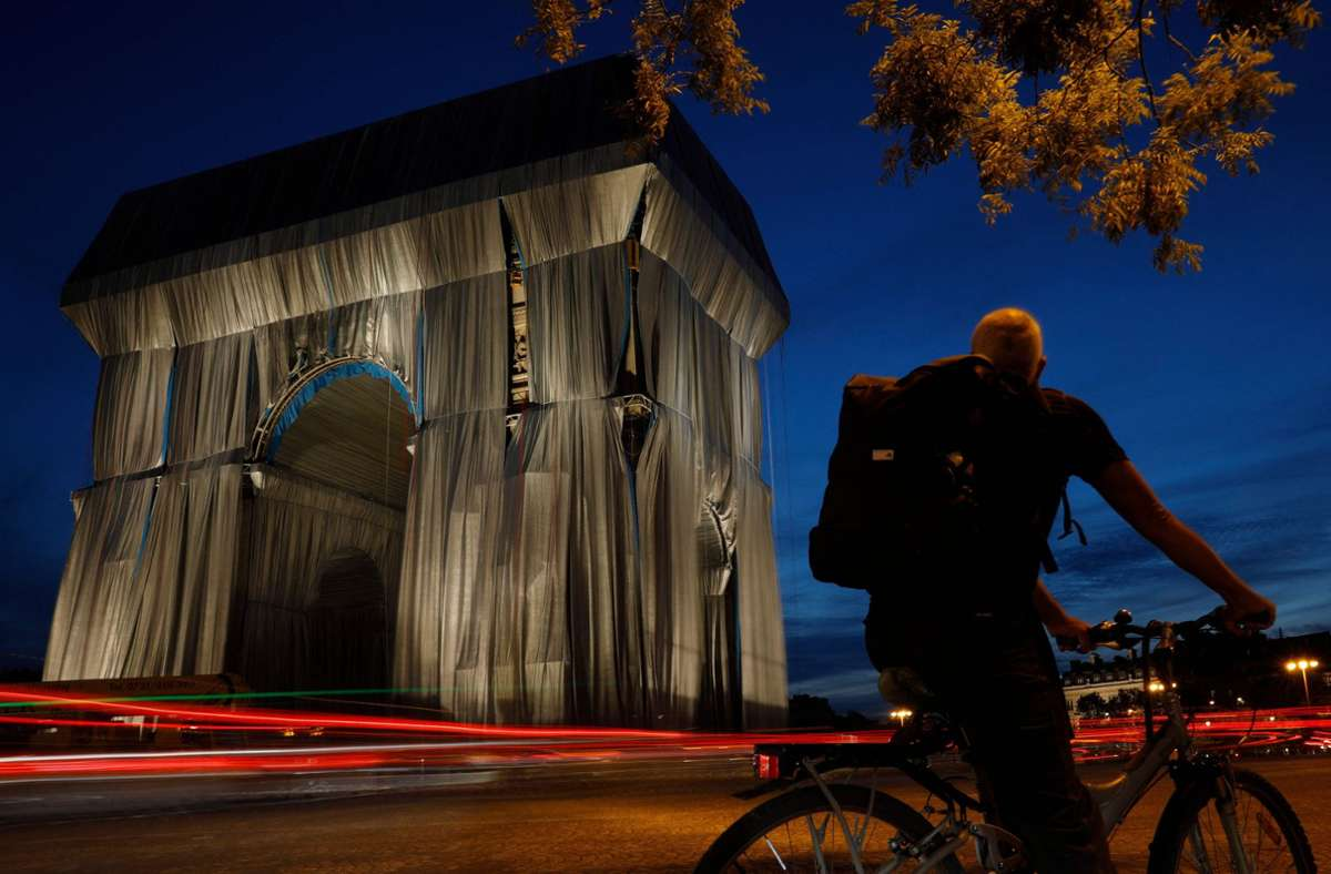 Noch nicht ganz fertig und schon ein Besuchermagnet. Der Arc de Triomphe in Paris wird nach Plänen des verstorbenen Künstlers Christo verhüllt. Foto: AFP/GEOFFROY VAN DER HASSELT