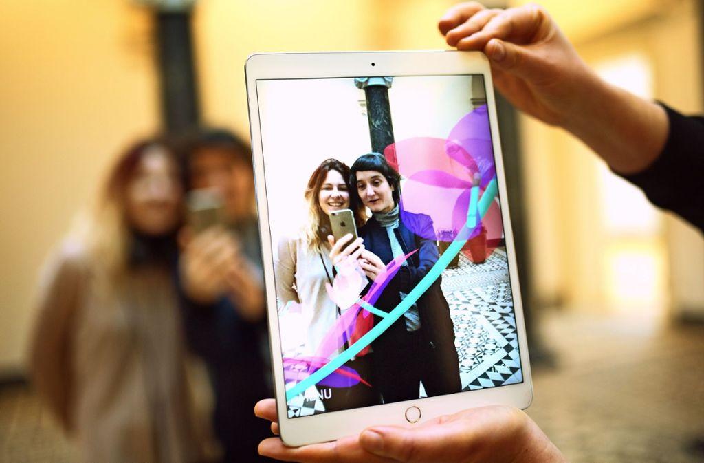 Barbara Herold (rechts) führt  die  virtuellen Pflanzen vor.  Ein Handy und etwas Spielfreude sollten Nutzer mitbringen. Foto: Ines  Rudel