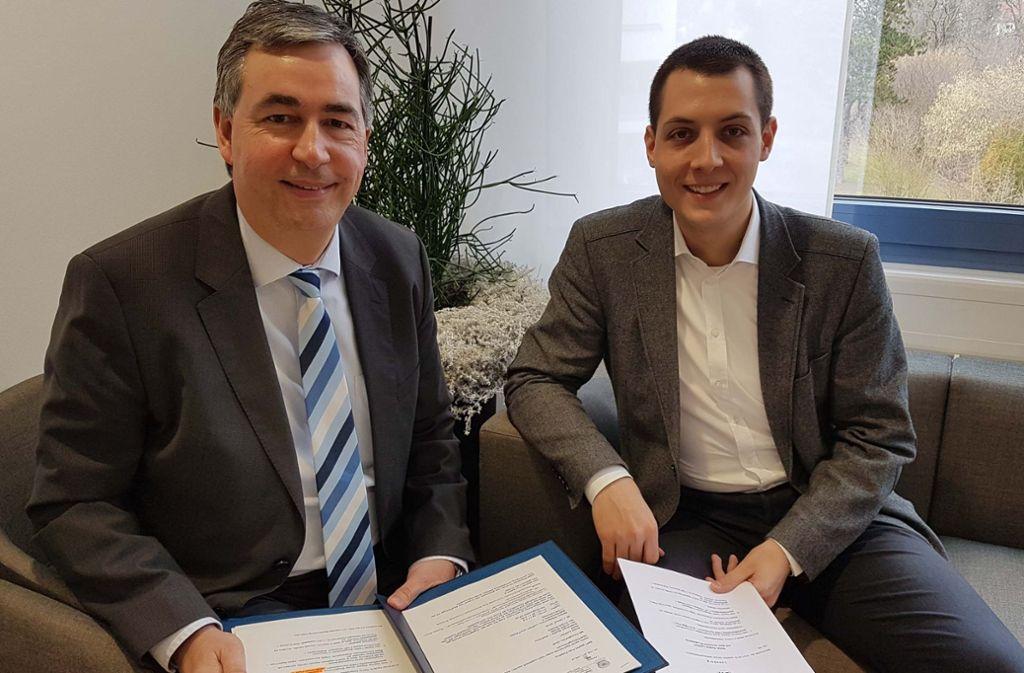 Dietmar Allgaier, der Erste Bürgermeister Kornwestheims, und Daniel Töpfer unterzeichnen den Kaufvertrag. Foto: Stadt Kornwestheim