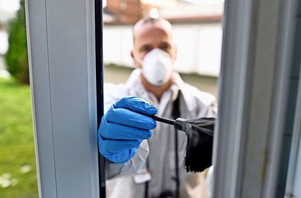 Ein Kriminalbeamter sichert  die Spuren nach einem Einbruch. Foto: dpa