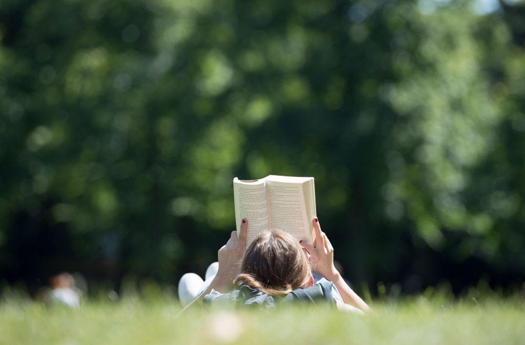 Mit einem guten Buch lässt es sich im Grünen bestens aushalten. Foto: dpa