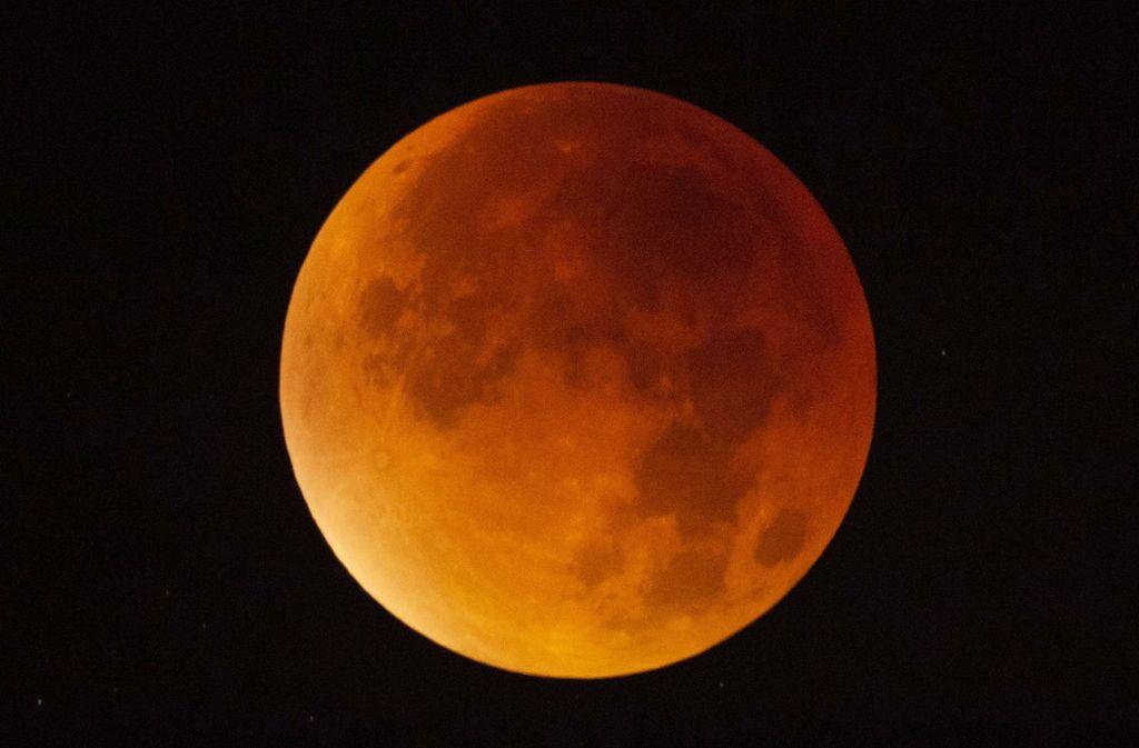 Bei einer totalen Mondfinsternis wird der Mond allerdings nicht etwa vollständig schwarz, sondern er leuchtet kupferfarben bis orangerot. Foto: dpa