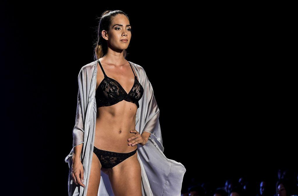 Ein Model präsentiert in Kolumbien Dessous aus schwarzer Spitze mit einem edlen Morgenmantel aus Seide während der Cali Exposhow Fashion Week. Foto: AFP