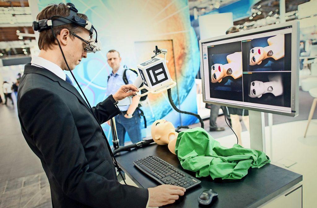 Ein Mitarbeiter am Fraunhofer-Institut für Graphische Datenverarbeitung bedient am Messestand in Hannover  ein sogenanntes Augmented-Reality-System, ein Kamerasystem, das speziell für den medizinischen Einsatz bei der Operation von Lymphknoten entwickelt wurde. Foto: dpa