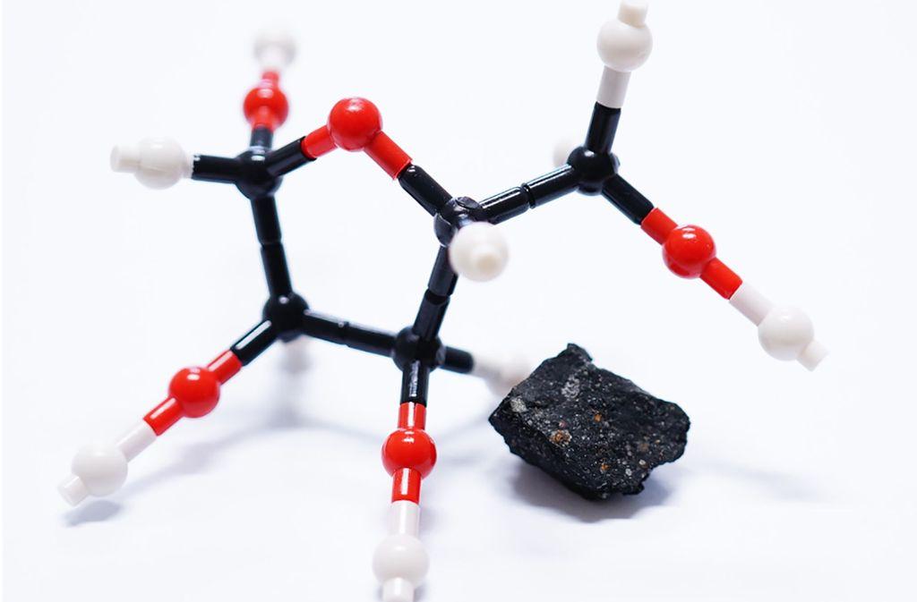 Ein Fragment des Murchison-Meteoriten liegt neben einem Molekularmodel des Zuckers Ribose. In dem 1969 in Australien niedergegangenen Gestein wurde Ribose, der zentrale Baustein des Erbgutmoleküls RNA (Ribonukleinsäure), gefunden. Foto: Yoshihiro Furukawa/Tohoku-Universität/dpa