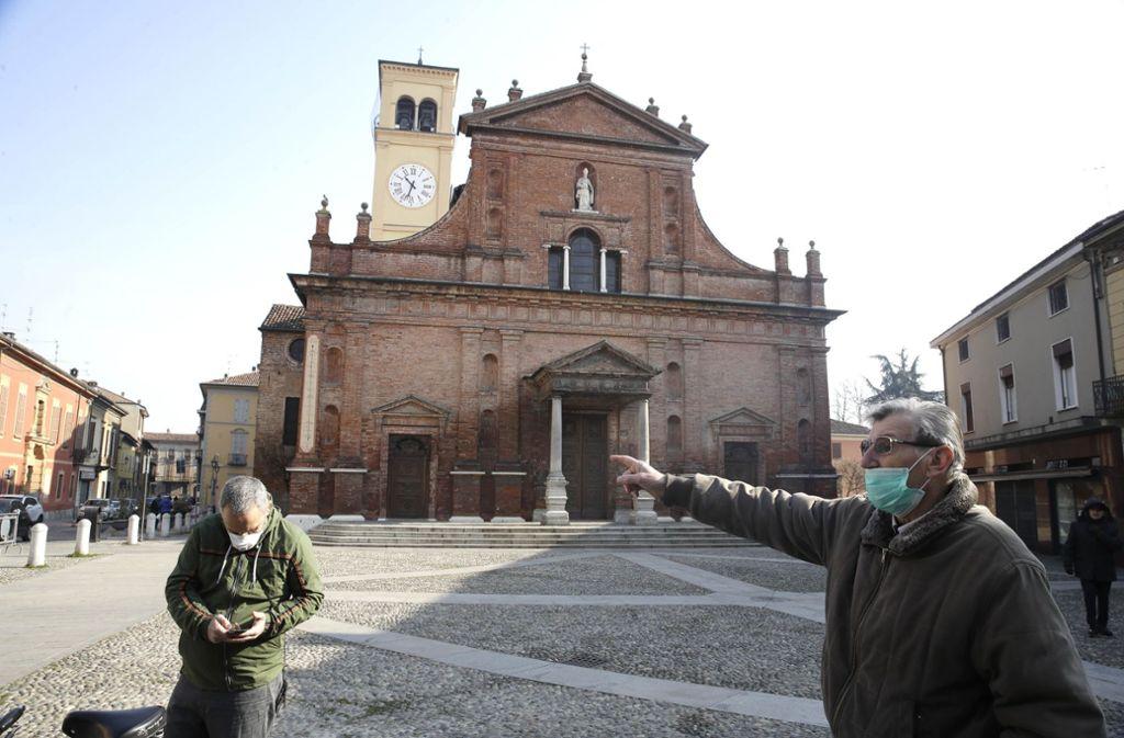 Zwei Männer Menschen mit Mundschutz stehen vor der Kirche San Biagio. In Italien soll die weitere Ausbreitung des Coronavirus mit drastischen Mitteln bekämpft werden. Foto: dpa/Luca Bruno