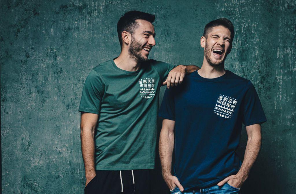 Die beiden Profis der TSG Hoffenheim, Sargis Adamyan (l.) und Andrej Kramaric, präsentieren T-Shirts aus der umoja-Kollektion. Foto: obs/Simon Hofmann