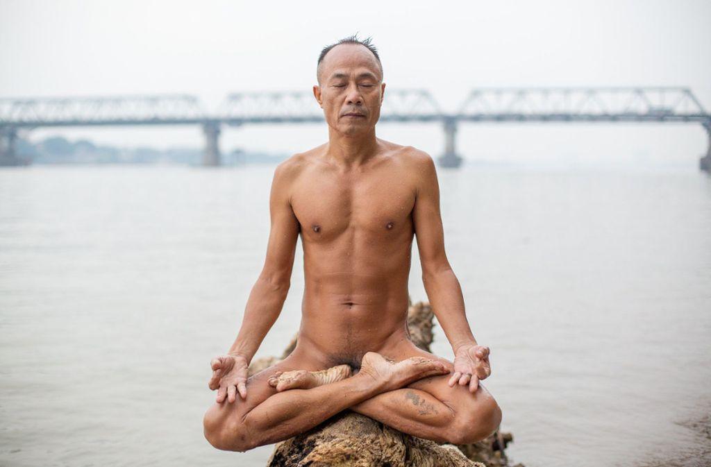 Do Duc Hoang, Anhänger der Freikörperkultur, genießt einen ruhigen Moment und meditiert auf einem umgestürzten Baum am Ufer des Roten Flusses. Foto: dpa/Chris Humphrey