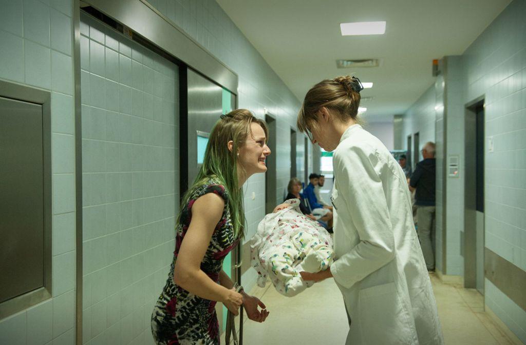 Nicole (Hanna Hilsdorf, l.) zeigt. Jana (Natalia Belitski) ihr schwer verletztes Baby. Foto: ZDF/Britta Krehl