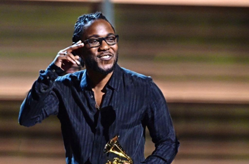 Kendrick Lamar grüßt freundlich – mit einem seiner fünf Grammys Foto: AFP