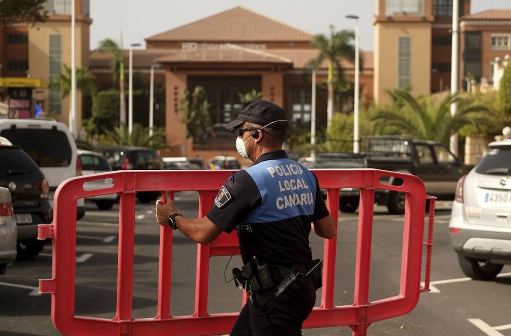 Eine Polizistin setzt eine Sperre, die den Zugang zum Hotel H10 Costa Adeje Palace auf Teneriffa blockiert. Nach einem bestätigten Coronavirus-Fall ist das Hotel unter Quarantäne gestellt worden. Foto: dpa/Uncredited