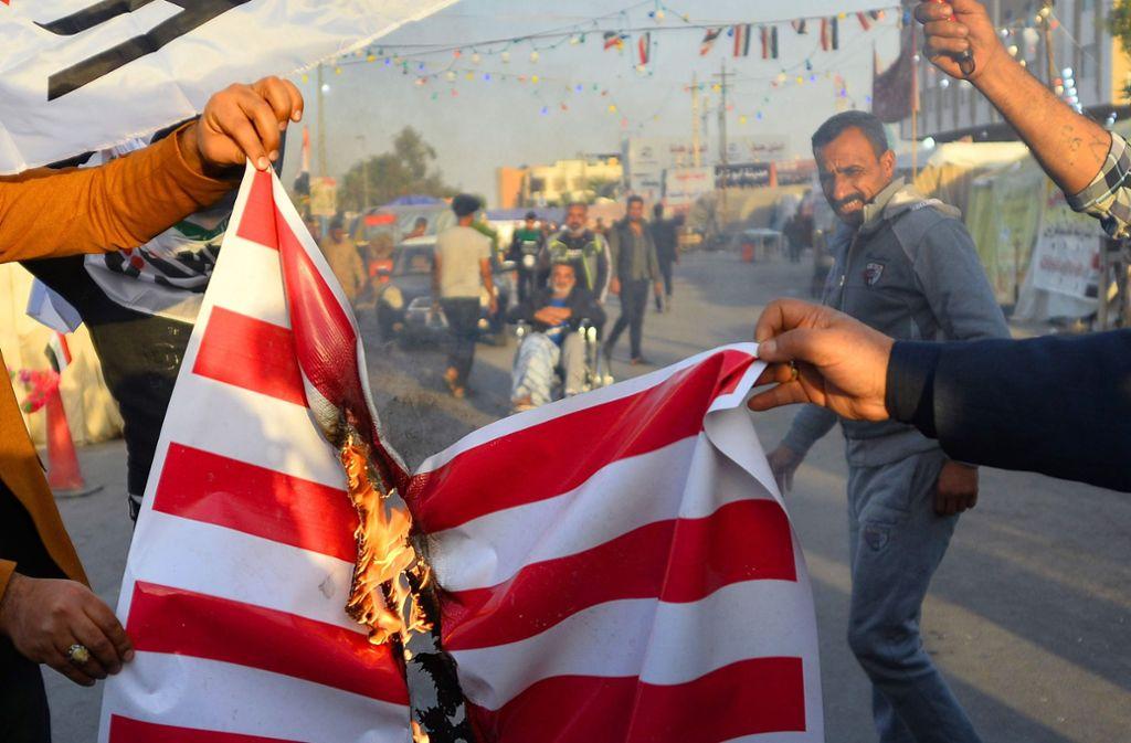 Menschen im Irak verbrennen die US-amerikanische Flagge. Foto: AFP/HAIDAR HAMDANI
