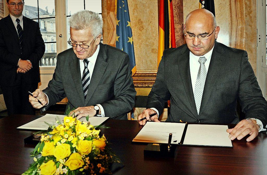 Ministerpräsident  Kretschmann und der Landesvorsitzende Daniel Strauß  haben 2013 den Staatsvertrag unterzeichnet. Foto: dpa