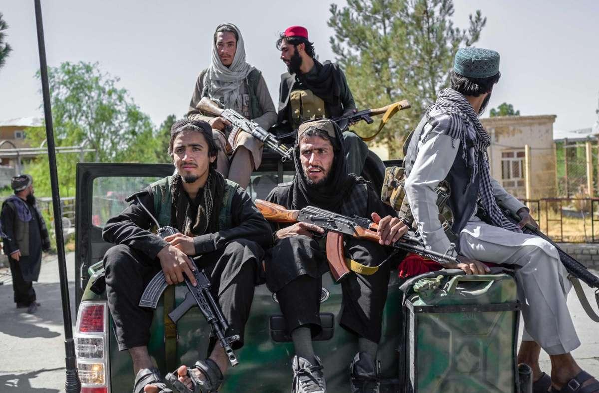 Taliban-Kämpfer posieren schwer bewaffnet auf Pick-ups. Einige von ihnen sind geschminkt. Foto: AFP/BULENT KILIC