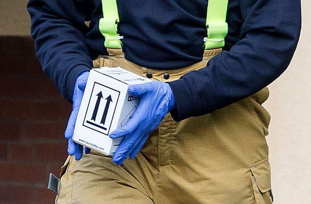 Ein Mitarbeiter der Feuerwehr trägt einen Karton mit Proben aus einem Mehrfamilienhaus in Hannover. Foto: dpa