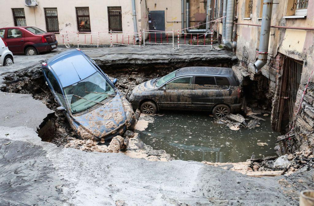 Auf Bildern war zu sehen, dass vor dem Café die Straße einbrach und zwei Autos darin versanken. Foto: TASS