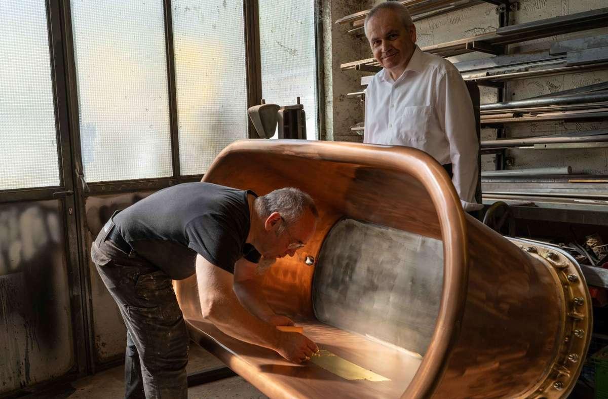 Der Künstler Edgar Harwardt beobachtet, wie Bernd Höger das Innere der Kupferbadewanne vergoldet. Dabei werden dünne Goldplättchen mit einem Pinsel aufgetragen. Foto: Lichtgut/Julia Schramm
