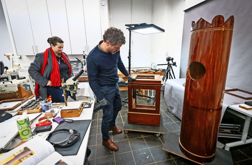 Die Restauratoren Frank Dornacher und Patricia Peschel inspizieren die Teile der 200 Jahre alten Uhr. Foto: factum/Granville