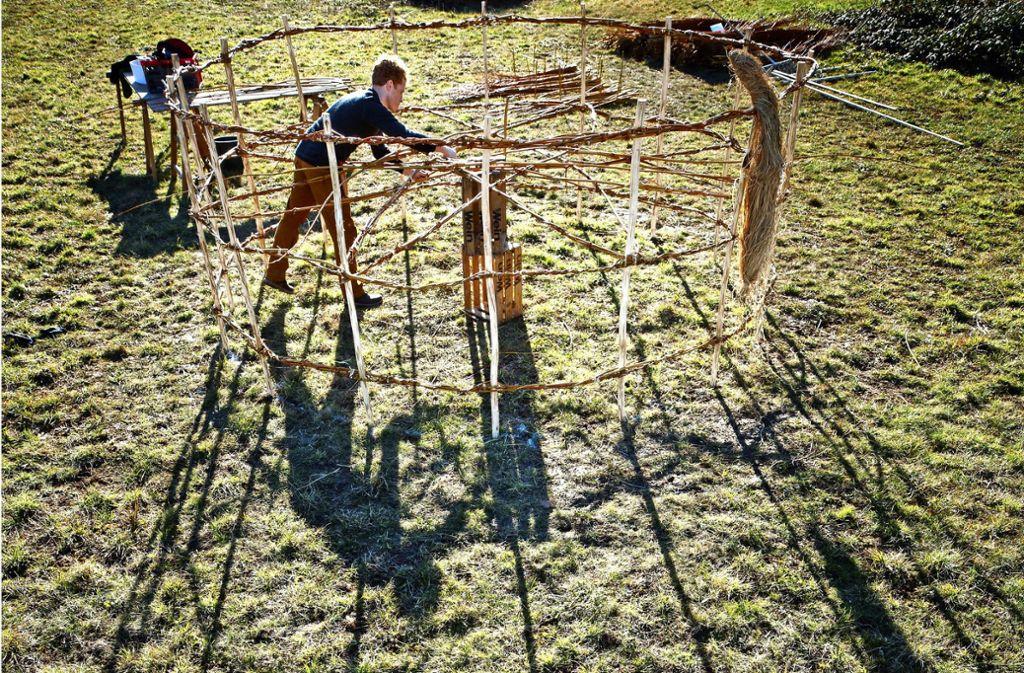 Noch liegt das Sonnenrad von David Klopp auf dem Boden, damit er besser daran arbeiten kann. Die Naturskulptur wird vier Meter hoch sein. Foto: Gottfried Stoppel